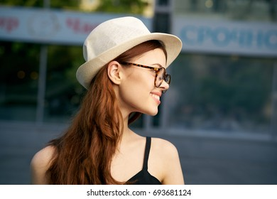 Young beautiful woman in hat and wearing glasses on the street in the city in summer, smile, portrait.