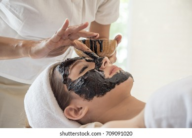 Young beautiful woman is having a black charcoal mask on her skin. Skincare and spa treatment.