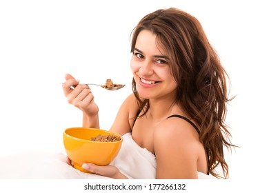 Young beautiful woman having breakfast in bed