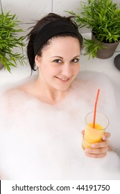 Young and beautiful woman is having a drink  in the bathtub
