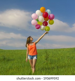 Young beautiful woman having fun with balloons on a green meadow
