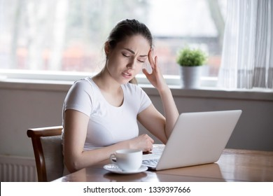 Young beautiful woman having headache working on computer at home. Millennial female sitting at table holding her head suffering from pain with eyes closed. Tired, overworked student, entrepreneur