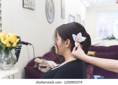 Young beautiful woman having her hair done at the hairdresser's, Stylist put flower in her hair