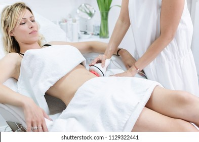 Young beautiful woman having radiofrequency stomach terapy in beauty spa salon.