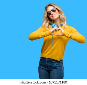 Young beautiful woman with headphones happy showing love with hands in heart shape expressing healthy and marriage symbol