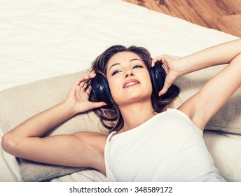 Young beautiful woman headphones listening music on bed
