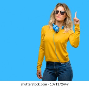 Young beautiful woman with headphones raising finger, the number one
