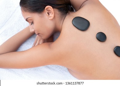 Young beautiful woman in health spa laying with eyes closed relaxing with heat volcanic stones on back, outdoors retreat. Healthy female enjoying leisure therapy wellness beauty lifestyle.