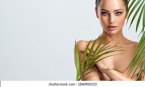 Young beautiful woman with healthy skin of body and palm leaves. Tanned body of an attractive white girl with green plants. Woman hiding her naked body with hands. Large palm leaves cover the body.