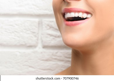 Young beautiful woman with healthy teeth smiling on light background