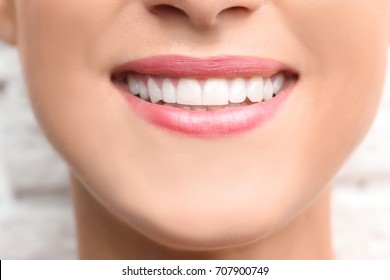 Young beautiful woman with healthy teeth smiling on light background, close up