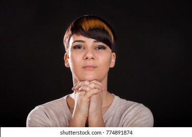 Young beautiful woman in her 20s with bicolor short haircut praying on black background. Studio portrait