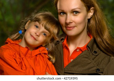 The young beautiful woman and her daughter smile against green trees.