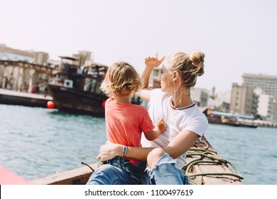 Young beautiful woman with her little son sitting at boat and contemplating the seascape of Dubai