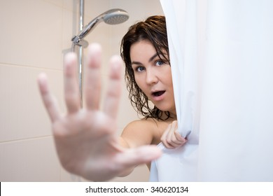 young beautiful woman hiding behind shower curtain