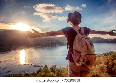 Young beautiful woman hipster traveler looking at sunset and beautiful seascape with a lookout point. Freedom, travel, vacation