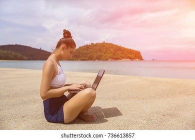 Young beautiful woman hipster traveler freelancer with laptop on the seashore. Business and vacation concept. Toned