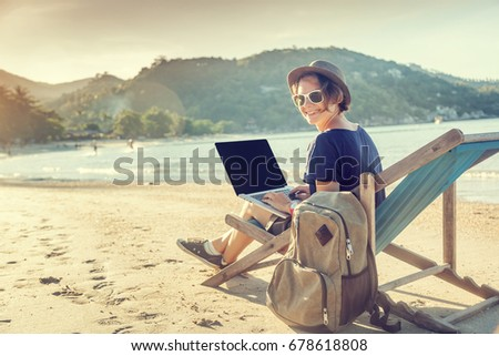 Young beautiful woman hipster traveler freelancer with laptop on the seashore. Business and vacation concept