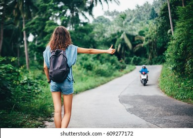 Young beautiful woman hitchhiking standing on road. Back view