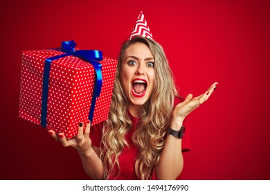 Young beautiful woman holding bitrhday gift over red isolated background very happy and excited, winner expression celebrating victory screaming with big smile and raised hands