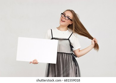 Young beautiful woman holding blank poster.Smiling woman sign board holding.Girl showing different emotions.Laughing, smiling, anger, suspicion, fear, surprise.