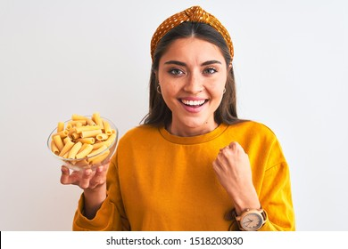 Young beautiful woman holding bowl with macaroni pasta over isolated white background screaming proud and celebrating victory and success very excited, cheering emotion