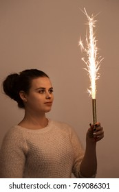 Young beautiful woman holding a burning firework