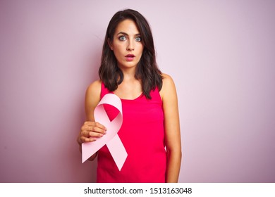 Young beautiful woman holding cancer ribbon over pink isolated background scared in shock with a surprise face, afraid and excited with fear expression
