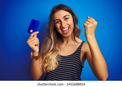 Young beautiful woman holding credit card over blue isolated background screaming proud and celebrating victory and success very excited, cheering emotion