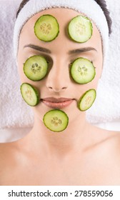 Young beautiful woman holding cucumber slices on the face in a spa salon.