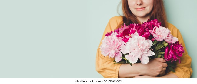Young beautiful woman holding flowers. Young girl in a yellow jacket holding big bouquet with fragrant peonies on light blue background. Birthday celebration concept