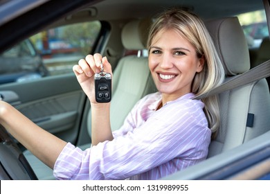 Young beautiful woman holding her car keys and smiling