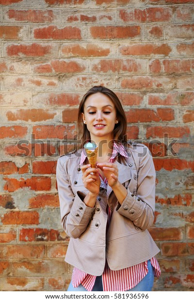 Young beautiful woman holding ice cream in hand