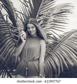 young beautiful woman holding mango and staying next to the palm tree