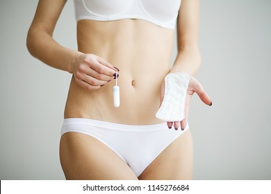 Young beautiful woman holding a menstruation cotton tampon and gasket in her hand, in a blurred background in white underwear.