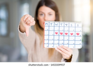 Young beautiful woman holding menstruation calendar at home with angry face, negative sign showing dislike with thumbs down, rejection concept