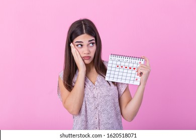 Young beautiful woman holding menstruation calendar over isolated background with surprise face. Young girl holding menstruation calendar with confused face, afraid and excited with fear expression