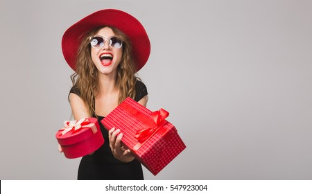 young beautiful woman holding presents, black dress, red hat, sunglasses, happy, smiling, sexy, elegant, gift boxes, celebrating, positive, emotional