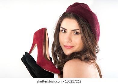 Young beautiful woman holding shoe in hand