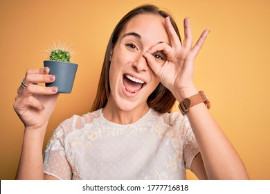 Young beautiful woman holding small cactus plant pot over isolated yellow background with happy face smiling doing ok sign with hand on eye looking through fingers