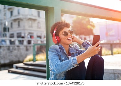 Young beautiful woman holding smartphone and listening to music with wireless headphones. Cheerful smiling girl with red headphones changing music track on phone. Carefree urban teen enjoying songs.