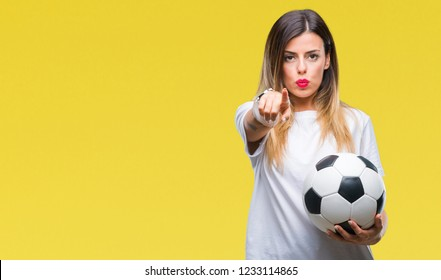 Young beautiful woman holding soccer ball over isolated background pointing with finger to the camera and to you, hand sign, positive and confident gesture from the front