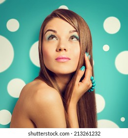 Young beautiful woman holding a turquoise bracelet with bright color manicure and makeup. Girl looking up. Vintage styled colors.