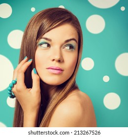Young beautiful woman holding a turquoise bracelet with bright color manicure and makeup. Girl looking to the side. Vintage styled colors.