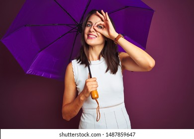 Young beautiful woman holding umbrella standing over purple isolated background with happy face smiling doing ok sign with hand on eye looking through fingers