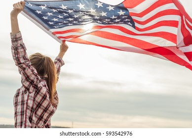 young beautiful woman holding USA flag.
