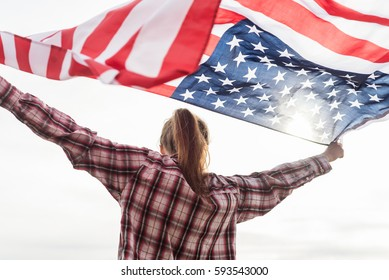 young beautiful woman holding USA flag.