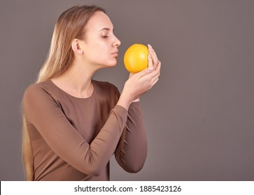 A young beautiful woman holds an orange in her hands and sniffs its smell.