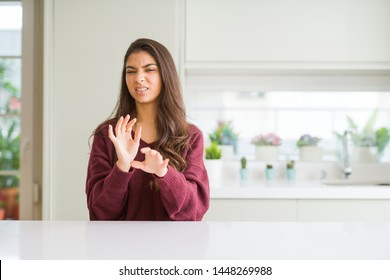 Young beautiful woman at home disgusted expression, displeased and fearful doing disgust face because aversion reaction. With hands raised. Annoying concept.