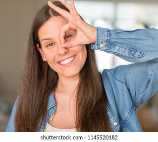 Young beautiful woman at home with happy face smiling doing ok sign with hand on eye looking through fingers